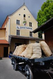 """Unsere Mühle und davor ein historischer """"Gaiwagen""""."""